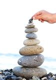 Pyramid of sea pebbles. Hand in building a pyramid from the sea pebbles Stock Photos