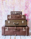 Pyramid of several vintage suitcases. On a pink background toned picture close-up shallow depth of field Stock Image