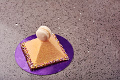 Pyramid shaped cake and macaron. Royalty Free Stock Photo