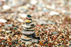 Pyramid of small stones built on a pebble beach. Pyramid of small flat stones built on a pebble beach Royalty Free Stock Photos