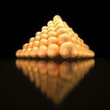 Pyramid som göras ut ur guld- fotbollbollar Royaltyfri Bild