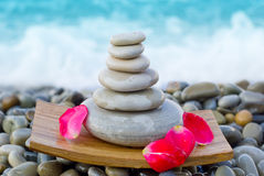 Pyramid from stones. Pyramid of stones with rose petals Royalty Free Stock Photography