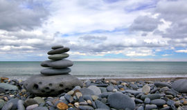 Pyramid of stones. On a sea beach with blue sky and clouds in the background Stock Photography