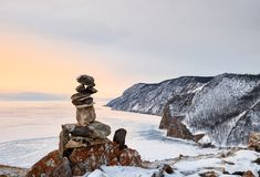 Pyramid of stones above ice lake. Dawn on Lake Baikal in March. Olkhon Island. Irkutsk region. Russia Stock Image
