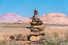 Pyramid of stones on the background of ridges in the steppes of Kazakhstan.  Stock Photos