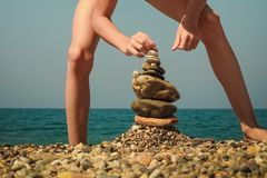 Pyramid of stones. Boy building stone stack on pebble beach on a background of sea Stock Photos