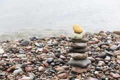 A pyramid of stones with a bright stone at the top stands on the sandy beach. The concept of leadership.  royalty free stock photos