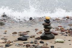 A pyramid of stones with a bright stone at the top stands on the sandy beach. The concept of leadership.  royalty free stock images