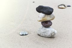A pyramid of stones with a bright stone at the top stands on the sandy beach. A pyramid of stones with a bright stone at the top stands on the sandy beach royalty free stock photos
