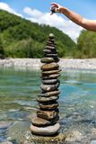 Pyramid of stones. Children`s hand puts pyramid of stones near mountain river on a background of blue sky with clouds royalty free stock image