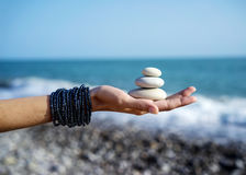 Pyramid of stones on female palm. Women's hands holds pyramid of stones on the palm on background of coastline, sea and sky Royalty Free Stock Photography