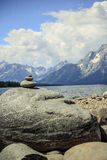 Pyramid of stones. On the lake beach with the mountain and lake view behind Royalty Free Stock Photo