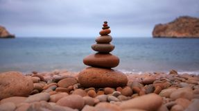 Sea in morocco. Pyramid of stones for meditation lying on sea coast Royalty Free Stock Image