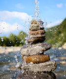 Pyramid of stones beside a mountain river. On which pours water Stock Photography