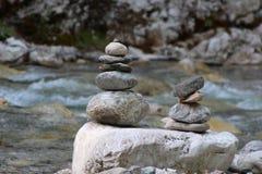A pyramid of stones. Near the mountain river Stock Photos
