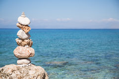 Pyramid of stones at the ocean. Blue water background. Stock Photos