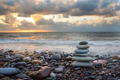 Pyramid of stones from pebble for meditation, on a background a seashore at sunset a sun. Marine background.  royalty free stock photo