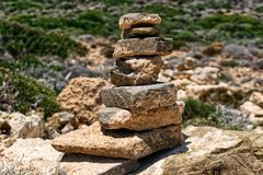Pyramid of stones. In nature in Prasonisi, Rhodes, Greece. Rocks and plants in the background royalty free stock images