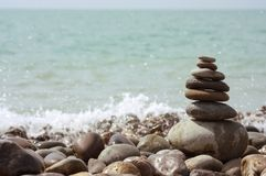 Pyramid of stones. Against the background of the sea with horizon Stock Photography