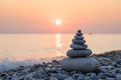 Pyramid of stones on sea coast Stock Image