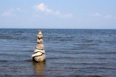 Pyramid from stones standing in the water on the coast of Estonia. Chudskom lake stock images
