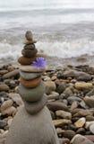 Stones pyramid symbolizing zen harmony balance. Pyramid stones symbolize the balance of Zen harmony amid the turbulent sea Stock Image