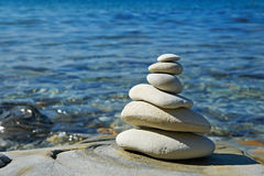 Pyramid of stones zen balance in sea shore. On sunny day stock photography