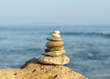 Pyramid of stones, zen concept. Placed stones balanced on a rock on the beach royalty free stock photos