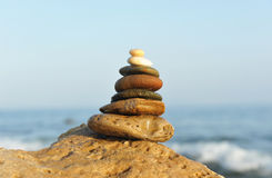 Pyramid of stones, zen concept. Placed stones balanced on a rock on the beach royalty free stock images