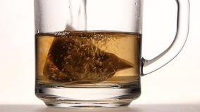 Pyramid tea bag in cup is poured over boiling water. Brewed tea, pure glass transparent mug with handle, water is colored brown, side view, white studio stock footage