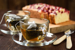Pyramid tea bags brewed in two glass cups and berry pie Royalty Free Stock Images