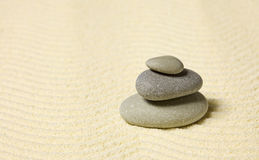 Pyramid of three stones on sand Royalty Free Stock Images