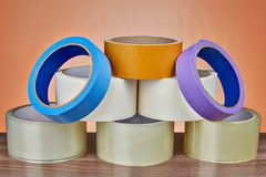 Pyramid of adhesive tape for various purposes, orange background royalty free stock photos