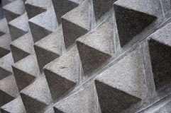 Pyramid wall. Looking sideways up a wall covered in small pyramids creating an unusual texture royalty free stock photos