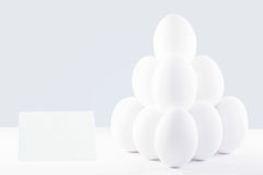 Pyramid of white chicken eggs with a price tag. Stock Photos