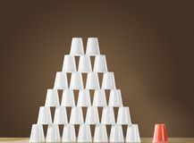 Pyramid of white plastic cups on table next to single red cup Royalty Free Stock Photos