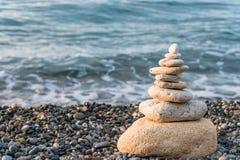Pyramid of white stones on a pebble beach close-up concept photo. Balance royalty free stock photos