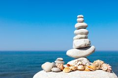 Pyramid of white stones and shells on a background of blue sky and sea royalty free stock image
