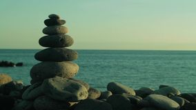 Pyramid of zen stones on a beach stock video footage