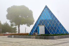 The pyramidal building and tree in fog Stock Photo