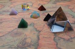 Pyramide cristalino y pequeñas pirámides de piedras preciosas naturales con el cubo ligero en un mapa del mundo antiguo fotografía de archivo
