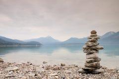 Pyramide de pedra equilibrado na costa, água azul do lago da montanha Fotos de Stock