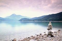 Pyramide de pedra equilibrado na costa, água azul do lago da montanha Fotografia de Stock