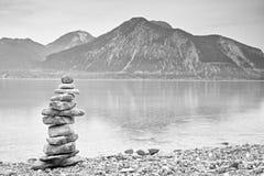 Pyramide de pedra equilibrado na costa, água azul do lago da montanha Imagens de Stock