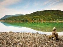 Pyramide de pedra equilibrado na costa da água azul do lago da montanha Montanhas azuis Imagens de Stock