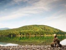 Pyramide de pedra equilibrado na costa da água azul do lago da montanha Montanhas azuis Imagem de Stock Royalty Free