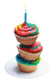 Pyramide de trois petits gâteaux colorés avec une bougie brûlante Photos libres de droits