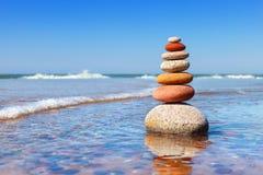Pyramide de zen de roche des cailloux colorés se tenant dans l'eau sur le fond de la mer Concept de l'équilibre, harmonie et images stock