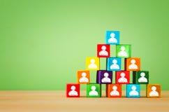 Pyramide der hölzernen Blöcke mit Leuteikonen, Personalwesen und Managementkonzept Lizenzfreies Stockbild
