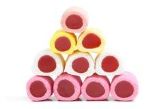 Pyramide des bâtons colorés de sucrerie sur le blanc Photo stock
